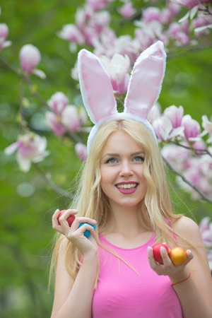easter eggs in had of happy girl or cute woman with long, blond hair, in rosy, bunny ears on blossoming magnolia, floral environment. Spring. Easter. Holidays, celebration 写真素材