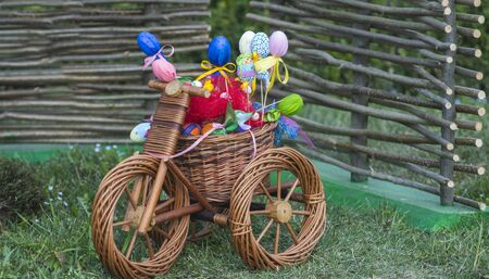 Wicker tricycle with easter basket on grass. Small bicycle with easter eggs. Happy easter celebration. Spring, season, festival. Stock Photo
