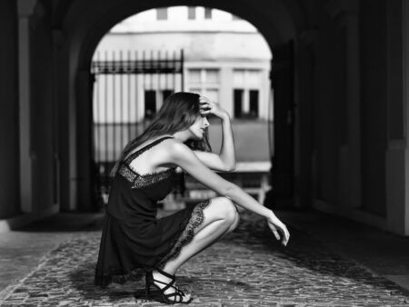 young stylish pretty sexy woman or girl with brunette hair in black dress sitting on paving stones road in street outdoor with arch 版權商用圖片