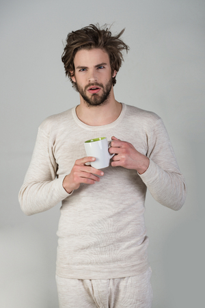 Morning with coffee or milk. Man with disheveled hair drink mulled wine. Sleepy guy with tea cup on grey background. Cold and flu, single. Insomnia, refreshment and energy.