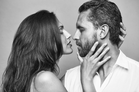 young sexy couple of bearded handsome man with beard and pretty woman or girl with long brunette hair embracing in studio on grey background Stockfoto