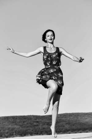 Pretty girl young beautiful woman brunette slim model with bare feet in sexy blue dress jumps on sky background Stockfoto