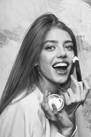 Happy pretty girl or beautiful woman with long, blond hair, putting facial cream or mask on young face skin with brush from jar and smiling on abstract rosy background. Cosmetology, beauty and spa 스톡 콘텐츠