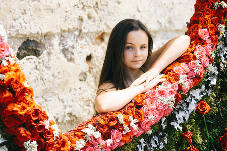 Little adorable girl stand near colorful rose flowers in spring garden