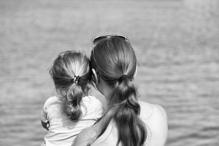 Mother and son, beautiful woman and cute baby boy, with blond hair ponytails look at sea or ocean water on sunny summer day on blurred blue background Stock Photo