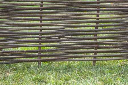 Fence of wooden twigs on green grass. Natural tree trunk texture. Garden decor, barrier, border, boundary. Spring, summer season 스톡 콘텐츠