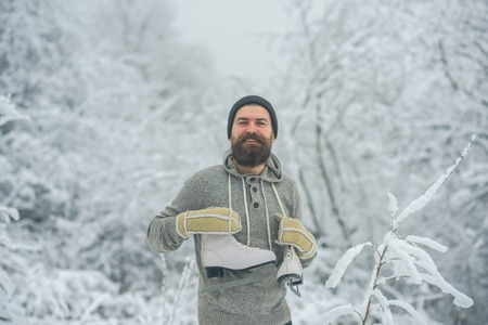 Man in thermal jacket, beard warm in winter. Winter sport and rest, Christmas. skincare and beard care in winter. Bearded man with skates in snowy forest. Temperature, freezing, cold snap, snowfall.