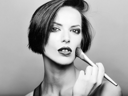 Pretty girl with short dark hair red lips and make up with face brush applies blush on her cheeks in front of grey background