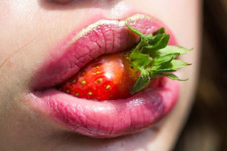 Strawberry in mouth with rosy lips, makeup. Beauty, lipstick, lip gloss, make up. Summer, fruit, berry, harvest season. Food, healthy diet, dieting. Nutrition, health, vitamin. 스톡 콘텐츠