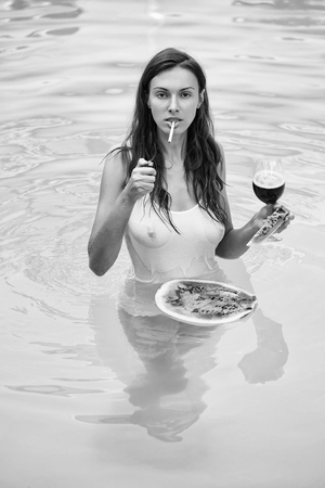 young sexy woman or girl with pretty face and long hair smoking cigarette in swimming pool with blue water in wet vest with bare chest holds red watermelon and wine glass summer day