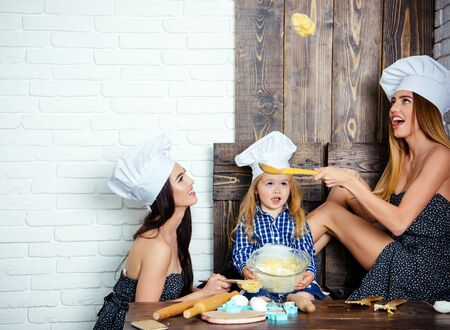 Women and child having fun with dough. Boy and girls in chef hats. Brother and sisters at table using kitchen utensils. Happy family and childhood concept. Homemade baking and cooking.