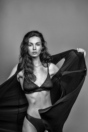 young sexy woman with pretty face and long brunette curly hair in black bra and panties has slim body in studio on grey background Standard-Bild