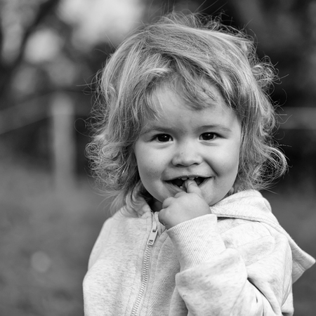 Kid little child baby boy fair-haired blond hazel-eyed smiling wearing grey hooded coat cute portrait with finger in mouth looking at camera on blurred natural background, square picture