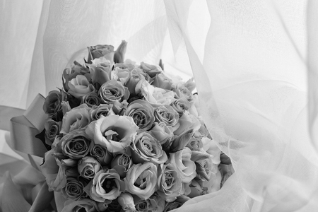 Photo closeup front view ball-shaped elegant wedding bouquet of fresh pastel pink white roses flowers buds with ribbons for bridal ceremony on white curtain lace background, horizontal picture  Stockfoto