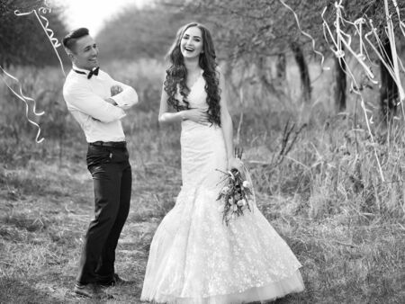 Happy newlywed couple posing and smiling in wedding dress and suit with flowers in forest decorated with ribbons outdoor