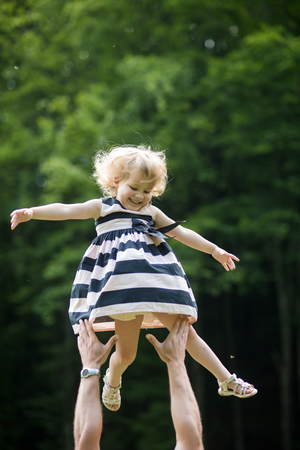 Girl smile flying to father hands on sunny summer day on natural environment. Freedom, future, optimism, support. Happy childhood concept Stock fotó
