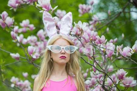 Spring, nature and environment. spring magnolia flower blossom and woman in bunny ears, easter
