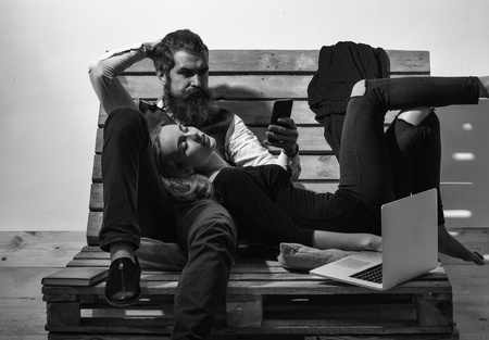Young couple spend time together with laptop, computer. Pretty girl or beautiful woman sleeps on knees of handsome man, bearded hipster with beard, talking on mobile phone on wooden pallet sofa