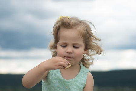Girl child eat cookie on summer day on cloudy sky. Food, diet, snack concept
