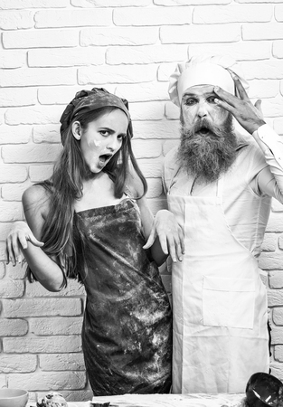 Messy pretty girl or beautiful woman and handsome man, cook or baker with flour on face, beard and moustache hug excited on white kitchen wall 版權商用圖片