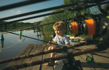 Little baby boy fishing on bank of river with fishing rod in hands. Banque d'images