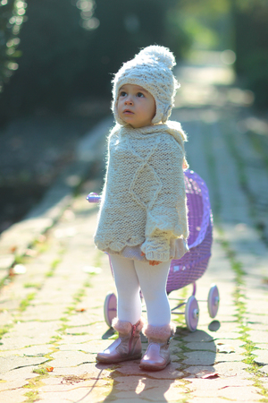 Toddler in knitted clothes playing outdoors. Role play games concept. Child and childhood lifestyle. Girl walking with vintage doll stroller on sunny day. Baby rolling violet toy carriage on park way.