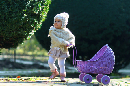 Girl walking with vintage doll stroller on sunny day. Baby rolling violet toy carriage on park way. Toddler in knitted clothes playing outdoors. Role play games concept. Child and childhood lifestyle.