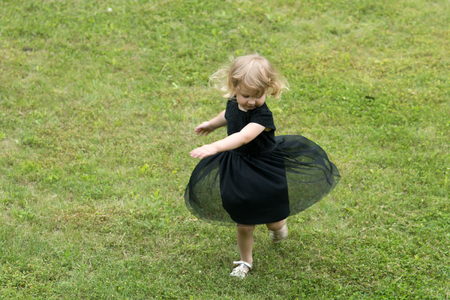 Girl with blond hair spin in black dress on green grass. Summer vacation, fun, joy, adventure concept.