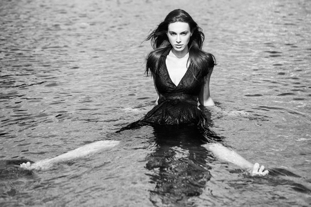 Sexy young girl in navy dress with long dark hair sits in water with legs apart
