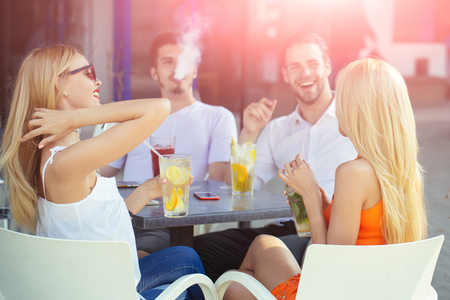 Man vapor hookah pipe in shisha bar lounge. Women twins and men friends relax in cafe outdoor. Celebration, party, proposal, birthday. Bad habits, party, addiction. Stock Photo