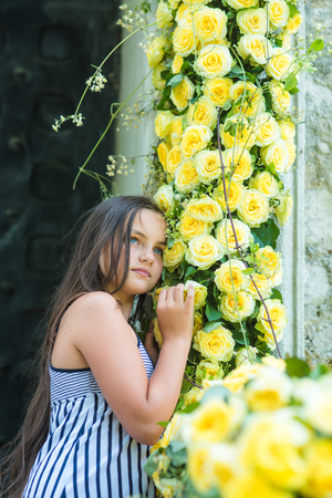 Little adorable girl smell yellow rose flowers at spring or summer day.