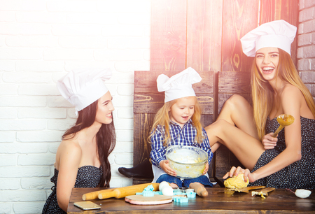 Brother and sisters at table using kitchen utensils. Homemade baking and cooking. Happy family and childhood concept. Child and women kneading dough. Boy and girls in chef hats.