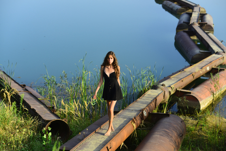 Woman walk on metal pontoon bridge over river. Girl in summer dress barefoot on iron construction on blue water. Summer vacation concept. Adventure, discovery, traveling, wanderlust. Stock Photo