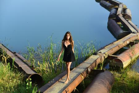 Woman walk on metal pontoon bridge over river. Girl in summer dress barefoot on iron construction on blue water. Summer vacation concept. Adventure, discovery, traveling, wanderlust. 版權商用圖片