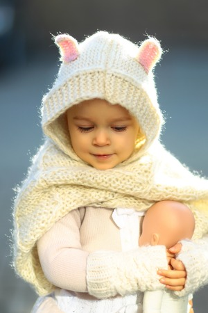 Girl baby in knitted hood and scarf playing with doll outdoors. Role play games concept. Child and childhood activities and lifestyle. 写真素材