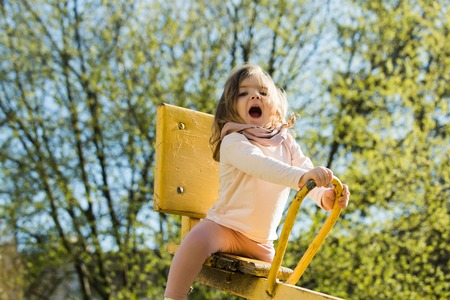 Happy child have fun on playground. Girl sit on seesaw on sunny day. Kid on teeter totter outdoor. Balance, equilibrium, harmony. Childhood, activity, lifestyle.