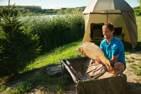Fishing adventures, carp fishing. Mirror carp, freshwater fish. Fisherman with big carp