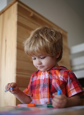 Painter child play with coloring book. Education and hobby. Small boy child drawing with colorful marker pen. Childhood and happiness, learning. Kid or blonde happy boy paint with felt pen.