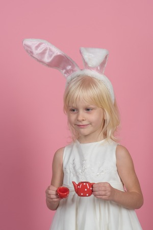 Tea mood, recipe, punchy pastel trend. Little girl in bunny ears, easter. Child smile with toy tea pot and cup. Kid beauty, fashion, look. Happy easter day. Spring holidays celebration. Banco de Imagens