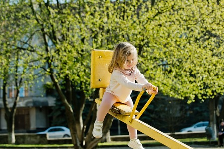 Balance, equilibrium, harmony. Girl sit on seesaw on sunny day. Kid on teeter totter outdoor. Child have fun on playground. Childhood, activity, lifestyle.