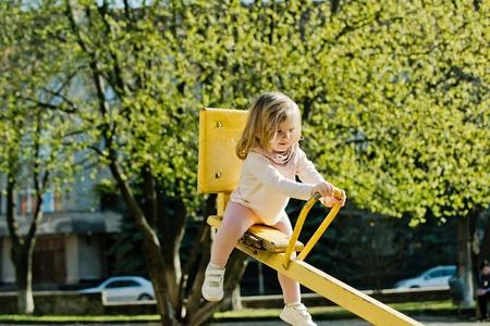 Evenwicht, evenwicht, harmonie. Het meisje zit op geschommel op zonnige dag. Het jonge geitje op wipplank wankelt openlucht. Kind veel plezier op de speelplaats. Jeugd, activiteit, levensstijl.