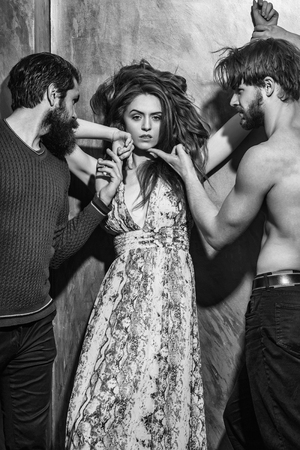 Pretty girl or beautiful woman with long brunette hair in sexy dress and two bearded men with beards, caucasian hipsters, in sweater and naked torso on yellow background