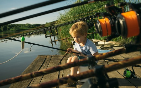 Adorable little boy fishing from wooden dock on lake in sunny summer day.