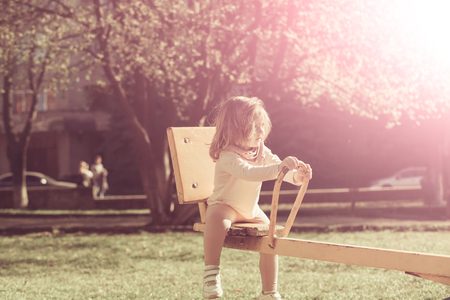 Girl sit on seesaw on sunny day. Child have fun on playground. Kid on teeter totter outdoor. Balance, equilibrium, harmony. Childhood, activity, lifestyle.