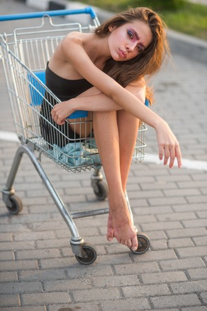 Girl ride shopping cart on pavement outdoor.