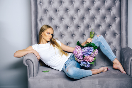 Woman with hydrangea flowers relax on sofa. Beauty, look, make up, skincare. Fashion, style, hairstyle. Womens day, 8 march, spring. Stock Photo