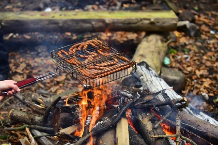 Autumn barbecue in nature - sausages fried on fire. Male hand holds grill over hot coals and fire flames.