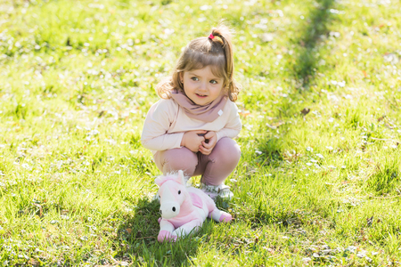 Child play with soft horse on green grass. Love, friend, friendship. Playing, game, toy concept. Stock Photo