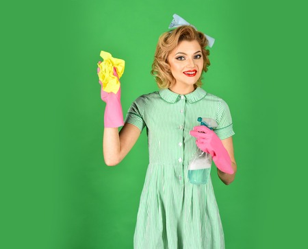 Cleanup, cleaning services, wife, gender. Cleaning, retro style, purity. Housekeeper in uniform with clean spray, duster. Stock Photo