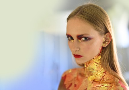 Halloween makeup, visage. Girl with blond hair, golden foil on skin, cosmetics. Skincare, skin treatment, therapy, copy space
